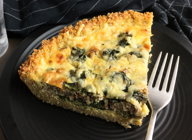 A wedge cut piece of spinach sausage quinoa crust quiche on a black round plate with a fork
