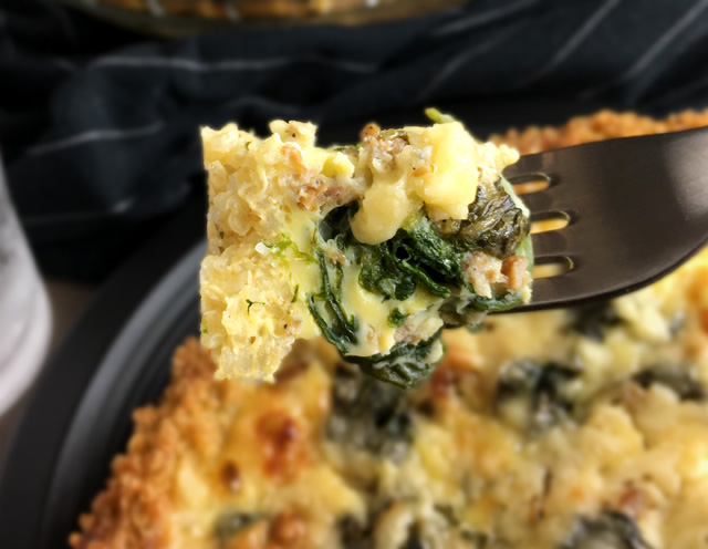 A forkful of spinach sausage quinoa crust quiche