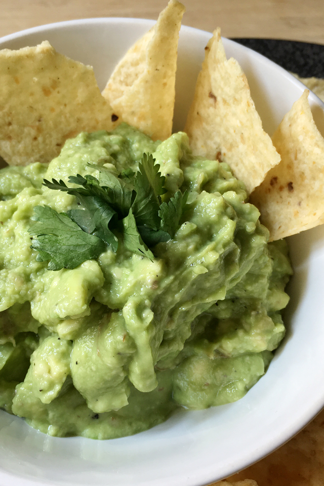 A close-up of a round white bowl containing super simple basic guacamole and yellow tortilla chips