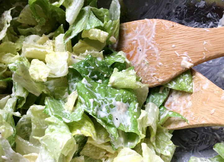 Two wooden spoons and chopped green lettuce with a white dressing in a bowl