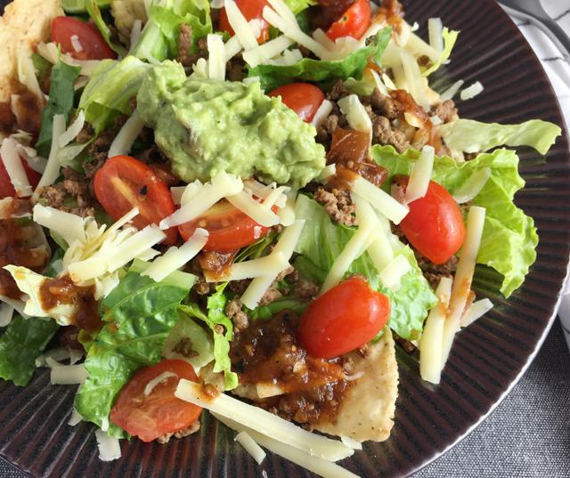 A dark round plate containing taco salad