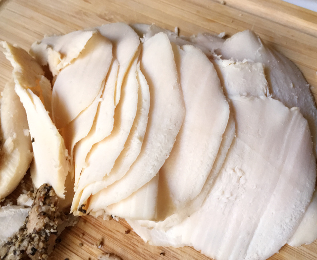 Slices of roasted chicken breast deli meat on a wooden cutting board