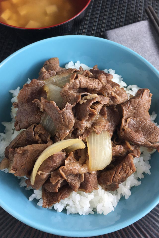 Close-up of a round blue bowl containing beef and onions on top of white rice for gyudon beef bowl