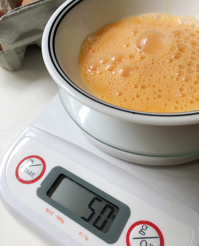 A white bowl containing raw egg sitting on a white scale with the number 50 on the screen for how to halve an egg