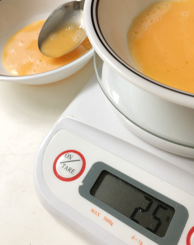 A white kitchen scale showing the number 25 on the screen and two white bowls containing raw egg for how to halve an egg