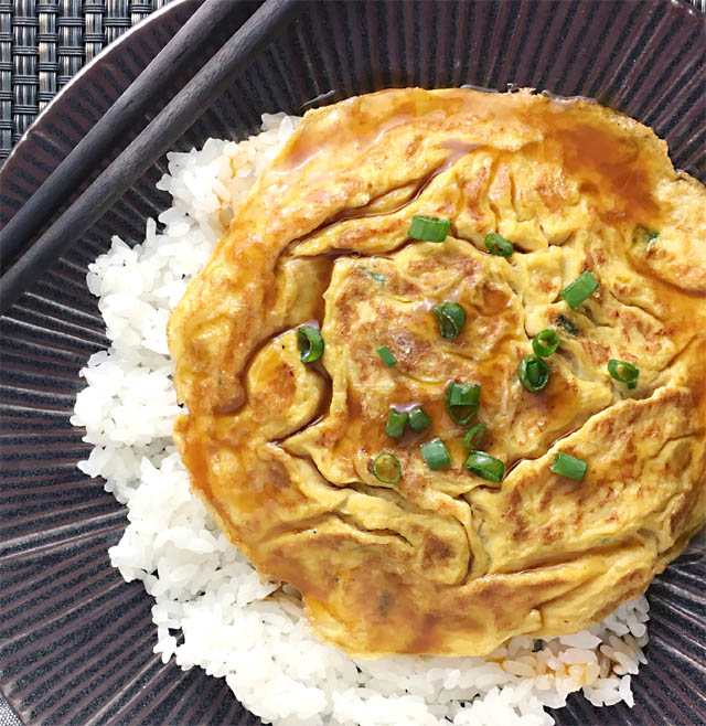 A dark round plate containing egg foo young omeltte on white rice topped with brown gravy