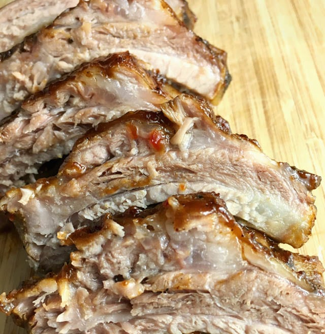 Several pork ribs on a wooden cutting board