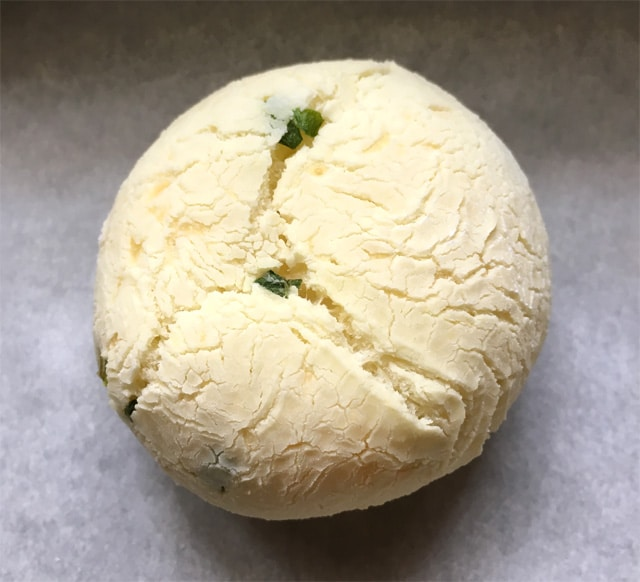 A round mochi ball with cracks on its surface and flecks of chopped green onion