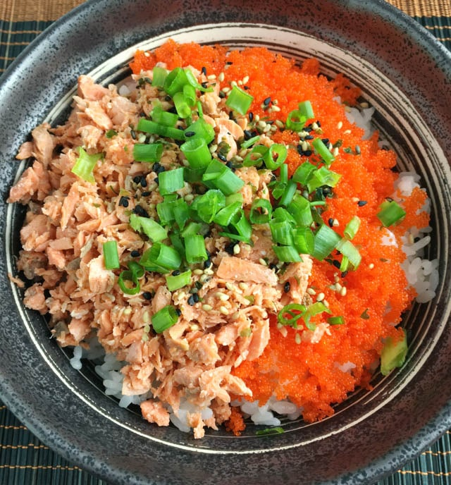 A dark round metal bowl containing orange flaked salmon, orange fish eggs, and chopped green onions