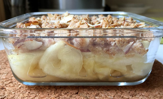 Side view of a glass dish containing yellow cooked apples topped with a brown crumbly topping