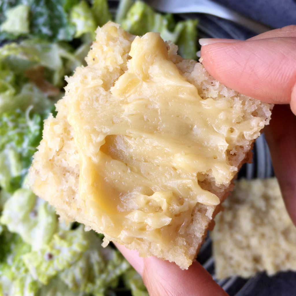 Close-up of a hand holding a square piece of cornbread with butter on top