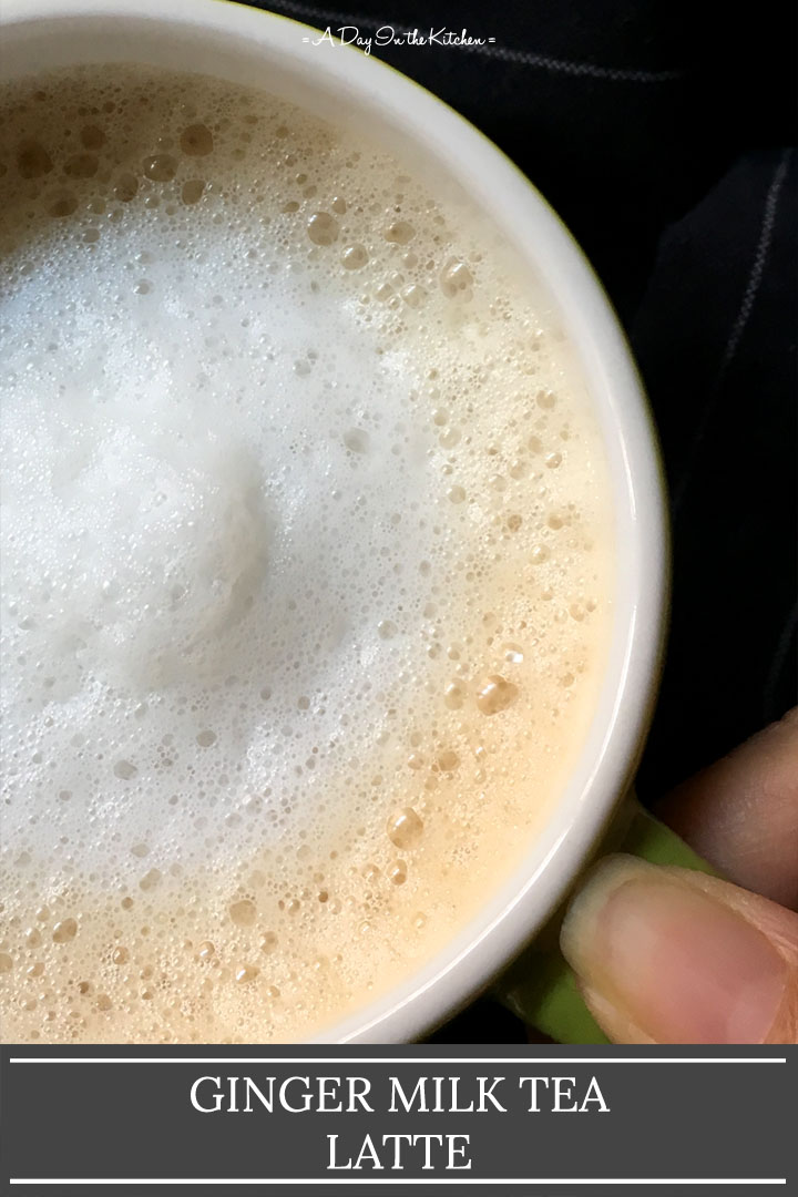 A handle holding the handle of a mug containing frothy tea, the words ginger milk tea latte on the bottom