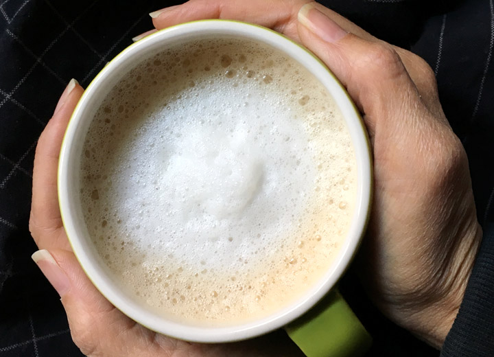 Two hands holding a cup of foamy tea
