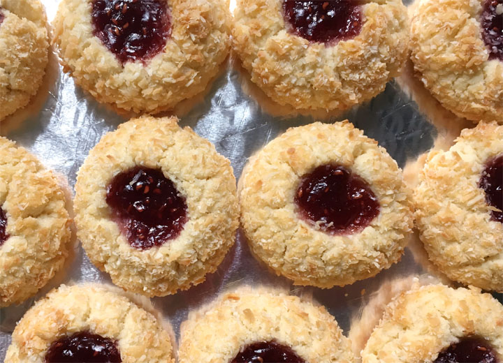 Several jam filled cookies on a foil sheet