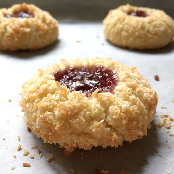 Closeup of a brown jam thumbprint cookie on parchment paper