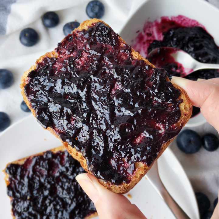 Fingers holding a piece of toast covered with purple blue jam