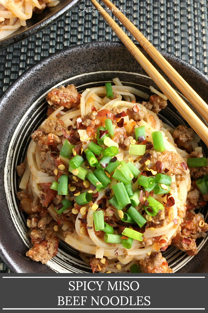 A pair of wood chopsticks resting on a round bowl containing noodles with ground beef and chopped green onions, the words spicy miso beef noodles on the bottom