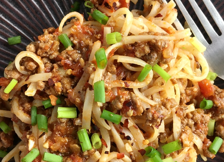 Close-up of flat thin flat noodles mixed with ground beef and tomatoes, topped with chopped green onions on a dark plate