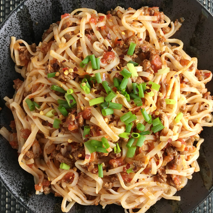 A round black bowl containing noodles, beef, tomatoes, and chopped green onions
