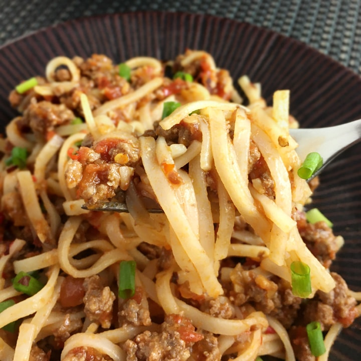 Close-up of a forkful of noodles and beef in a light tomato sauce