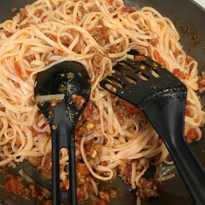 A black spoon and spatula in a round pan with noodles and ground beef and tomatoes