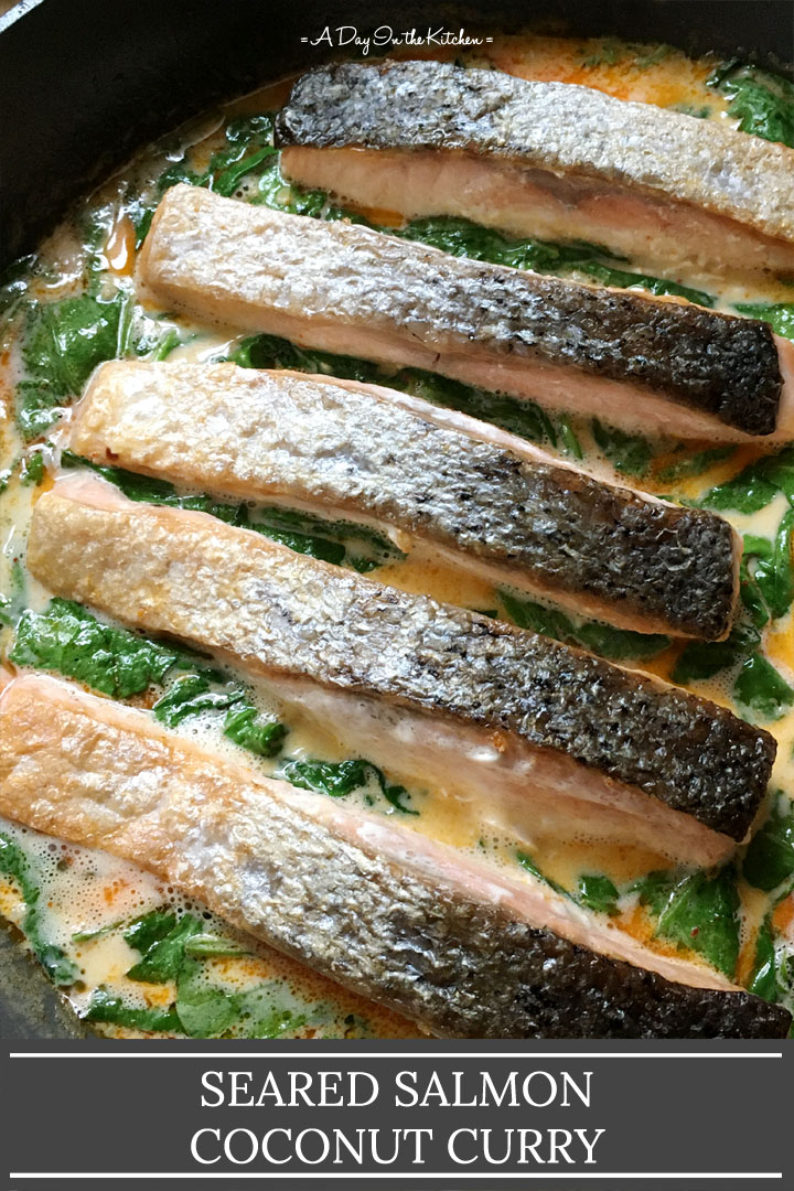 Five skin-on salmon filets in an orange sauce with green spinach, the words seared salmon coconut curry on the bottom