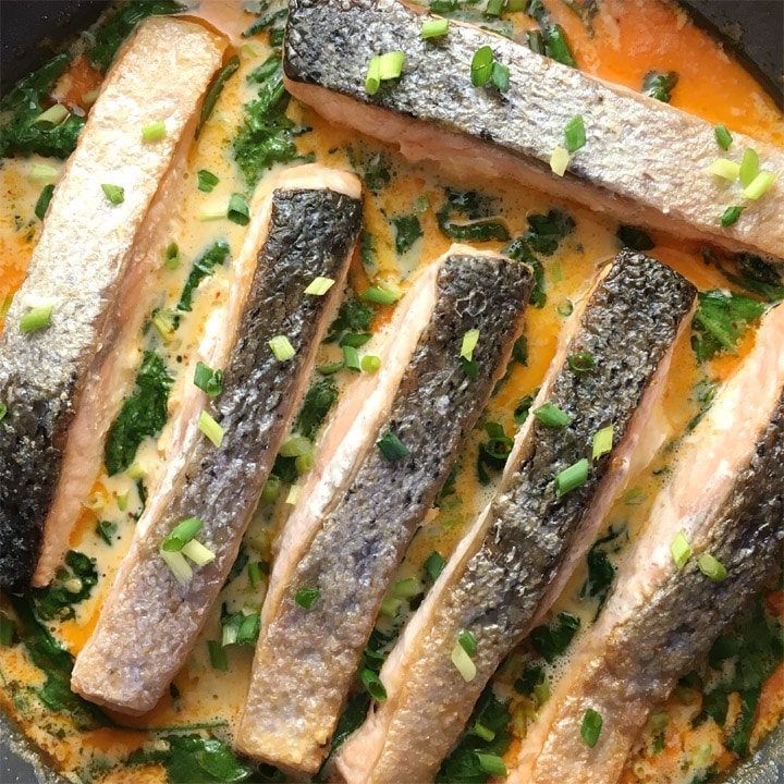Six skin-on salmon filets in an orange sauce with green spinach in a round pan