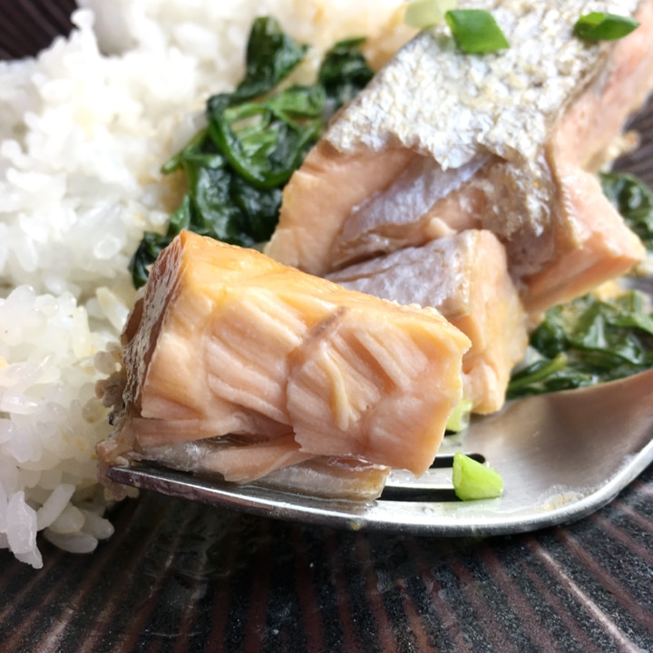 Close-up of a chunk of salmon on a fork, next to white rice, on a brown plate