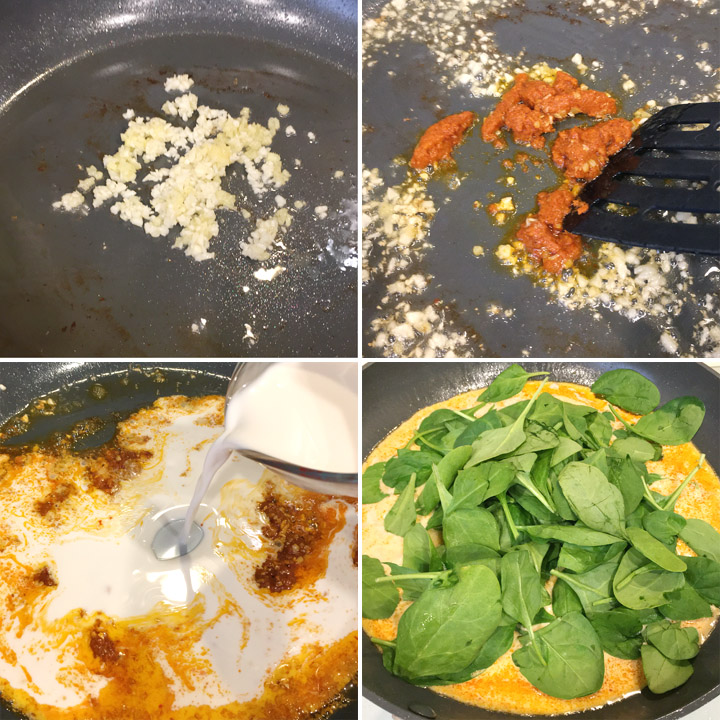 Minced garlic and ginger, red curry paste, white liquid, green spinach leaves being cooked in a round pan