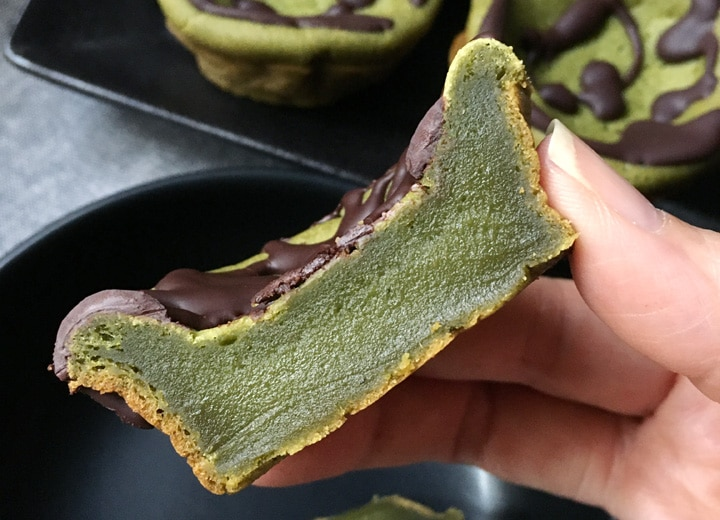 A hand holding a green piece of cake topped with brown chocolate