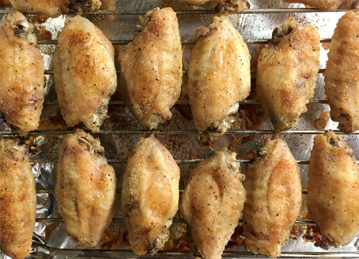Several brown baked chicken wings on a metal rack on a baking pan