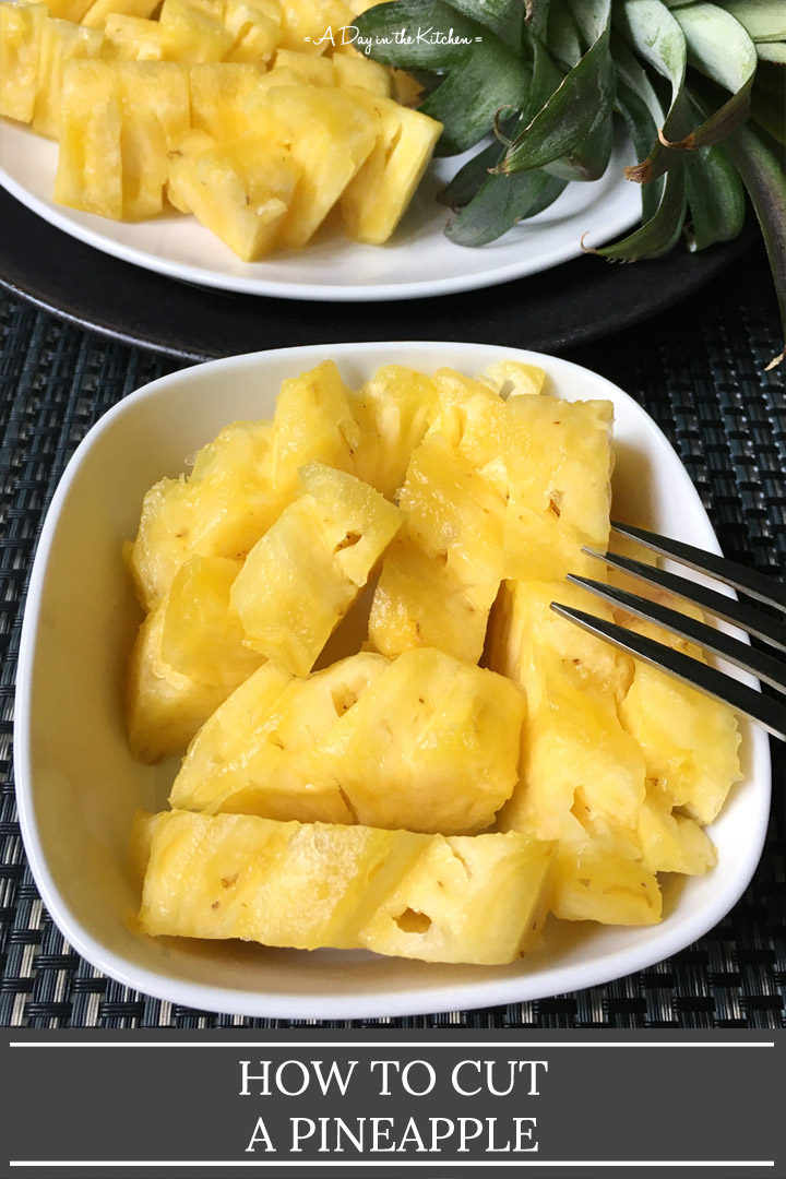 A fork resting on a white square bowl containing pineapple pieces, the words how to cut a pineapple on the bottom