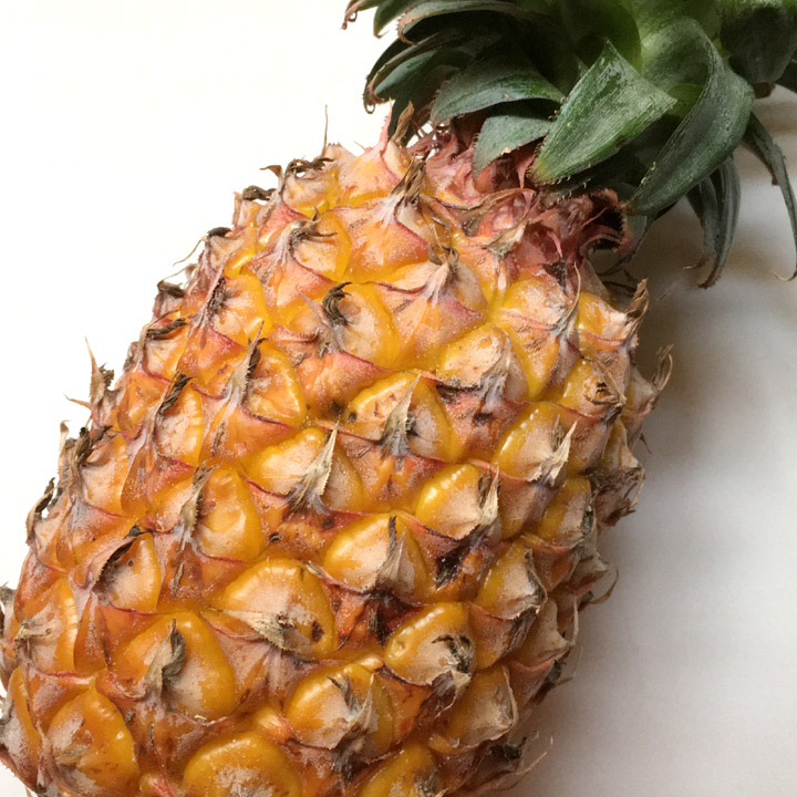 A yellow-orange skinned whole pineapple with green leaves