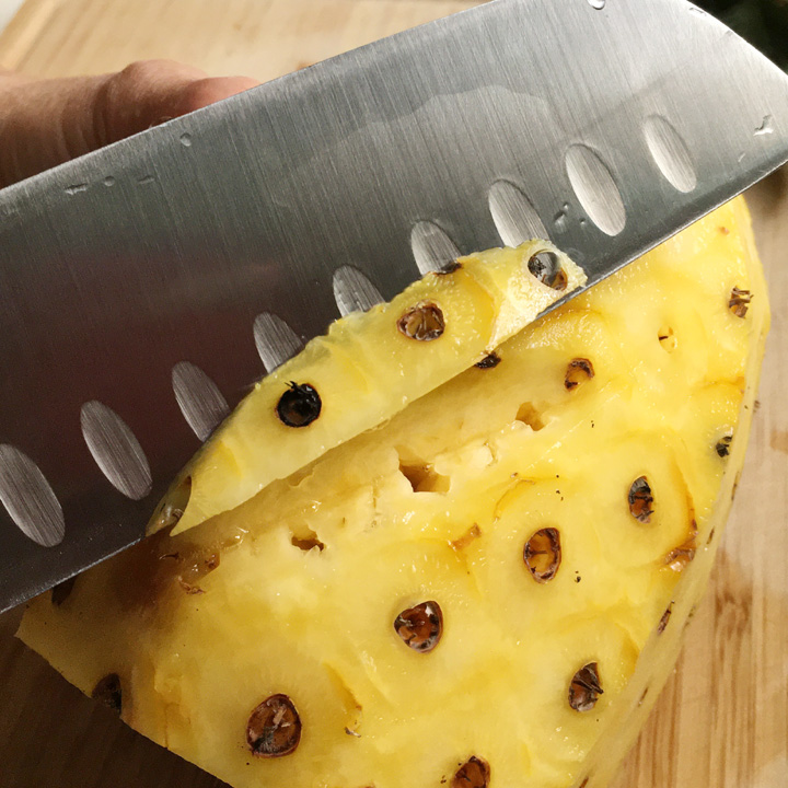 A knife cutting into a yellow peeled pineapple and removing brown circles