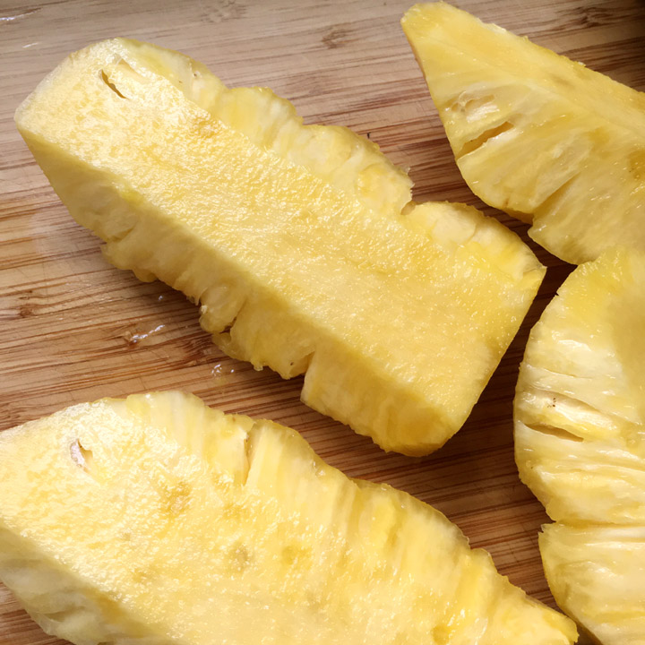 Long chunks of yellow pineapple on a wooden cutting board