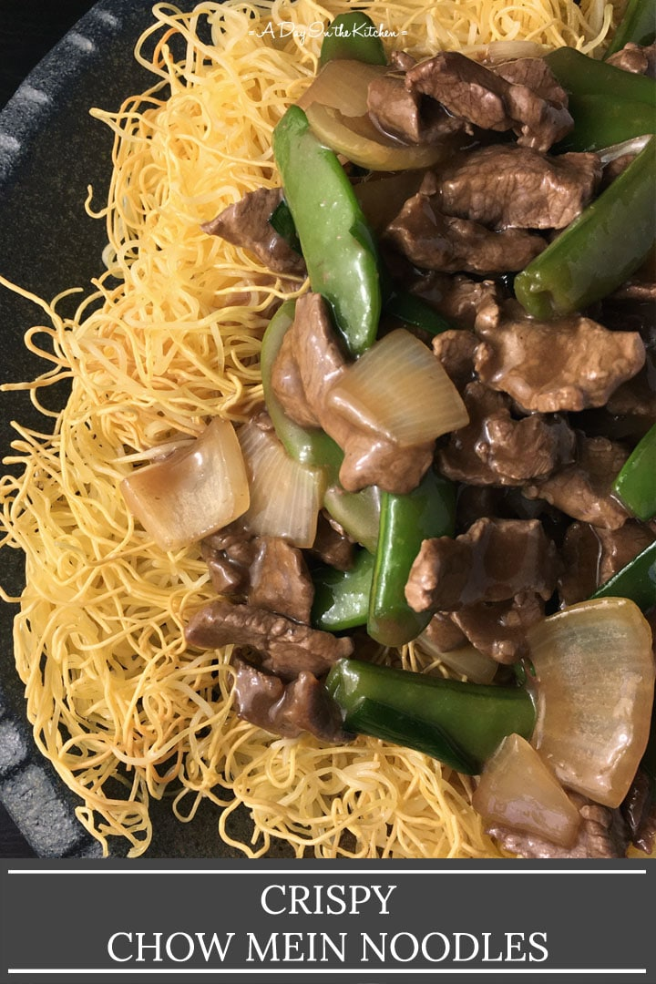 Slices of beef, green pea pods, chopped onions in a brown gravy over yellow noodles, the words crispy chow mein noodles on the bottom