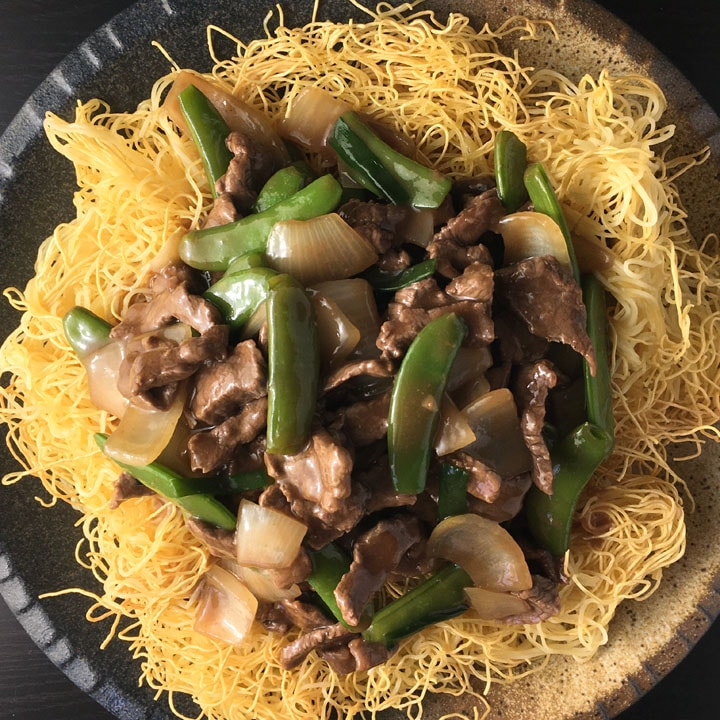 A round plate containing noodles topped with beef, green pea pods, and chopped onions in a brown sauce