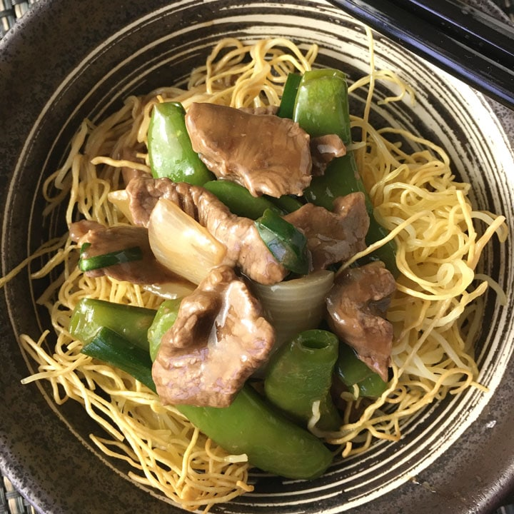 A bowl containing crispy chow mein noodles topped with beef and pea pods in a brown sauce