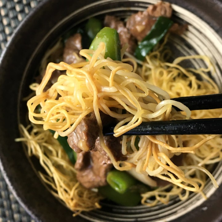Close-up of chopsticks holding noodles, beef, and a pea pod over a bowl of chow mein